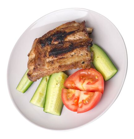 grilled pork ribs with sliced cucumbers and tomatoes on a light gray  plate. pork ribs isolated on white background. ribs grill top  side view Foto de archivo - 129862254