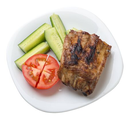 grilled pork ribs with sliced cucumbers and tomatoes on a white  plate. pork ribs isolated on white background. ribs grill top  side view Foto de archivo - 129862266