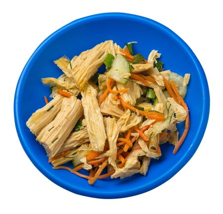 salad with soy asparagus and carrots, cucumbers and dumplings on a blue plate. vegetarian soy salad on a plate isolated on white background. healthy eating top sdie view. Foto de archivo - 129862269