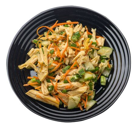 salad with soy asparagus and carrots, cucumbers and dumplings on a black  plate. vegetarian soy salad on a plate isolated on white background. healthy eating top sdie view. Foto de archivo - 129862279
