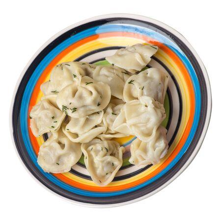 dumplings on a multicolored  plate isolated on white background .boiled dumplings.meat dumplings top side view .pelmeni with dill Foto de archivo - 129862278