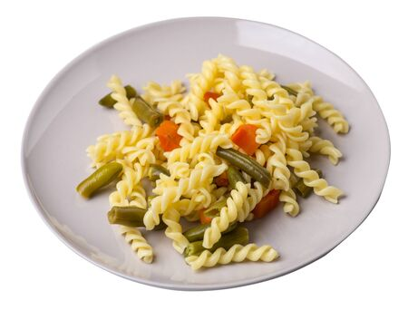 pasta with green beans with garlicand carrots on a light gray plate isolated on a white background. Mediterranean Kitchen . pasta with vegetables top side view. Foto de archivo - 129862283
