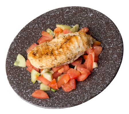 grilled chicken breast salad with tomato, cucumber and onion .grilled chicken breast on a  brown with a marble crumb  plate isolated on white background. grilled chicken breast top side view Foto de archivo - 129862306