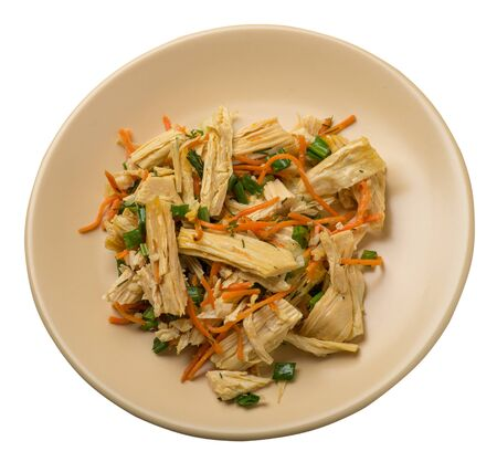salad with soy asparagus and carrots, cucumbers and dumplings on a light brown plate. vegetarian soy salad on a plate isolated on white background. healthy eating top sdie view. Foto de archivo - 129862308