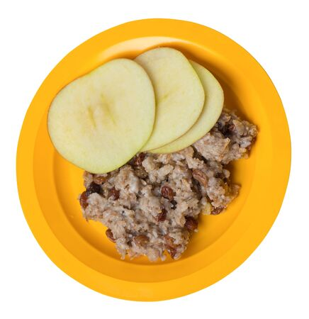 rye flakes with raisins and apples on a yellow plate. rage flakes isolated on white background. healthy breakfast top side view