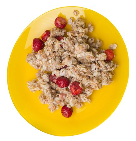 muesli with strawberries on a yellow  plate isolated on white background.healthy breakfast top side view.diet food on a plate.