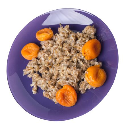 Healthy food .rzhanye flakes with dried apricots on a purple plate. rainy flakes isolated on white background. top side view diet breakfast