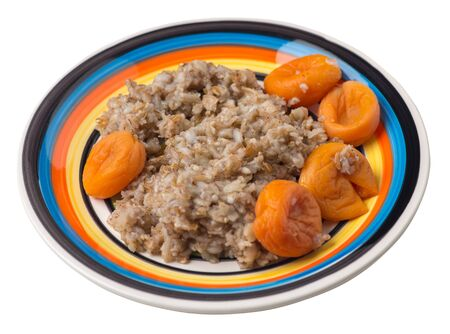 Healthy food .rzhanye flakes with dried apricots on a multicolored  plate. rainy flakes isolated on white background. top side view diet breakfast