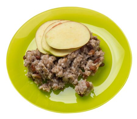 rye flakes with raisins and apples on a lime plate. rage flakes isolated on white background. healthy breakfast top side view
