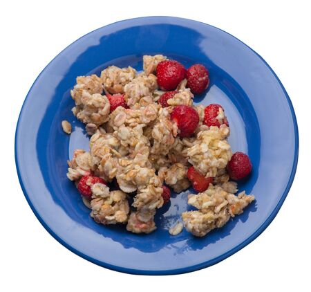 muesli with strawberries on a blue plate isolated on white background.healthy breakfast top side view.diet food on a plate.
