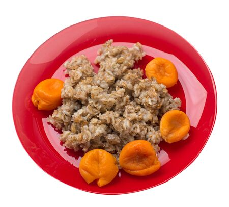 Healthy food .rzhanye flakes with dried apricots on a red  plate. rainy flakes isolated on white background. top view diet breakfast
