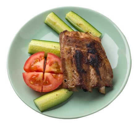 grilled pork ribs with sliced cucumbers and tomatoes on a light green  plate. pork ribs isolated on white background. ribs grill top  side view Stock Photo - 129862543