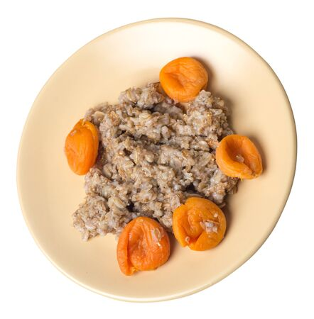 Healthy food .rzhanye flakes with dried apricots on a light brown plate. rainy flakes isolated on white background. top side view diet breakfast