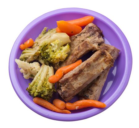 grilled pork ribs with broccoli cabbage, carrots and garlic on a purple plate. fried pork ribs with vegetables on a white background. hearty rustic food top side view Stock Photo - 129862564
