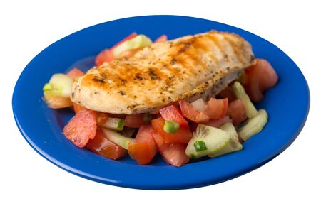 grilled chicken breast salad with tomato, cucumber and onion .grilled chicken breast on a blue plate isolated on white background. grilled chicken breast top side view Foto de archivo - 129862566