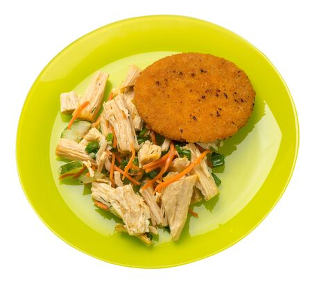 fishcake with soy asparagus and carrots, cucumbers and dilll.  fish cutlet on a lime plate isolated.fish cutlet with vegetables top side view Foto de archivo - 129862573