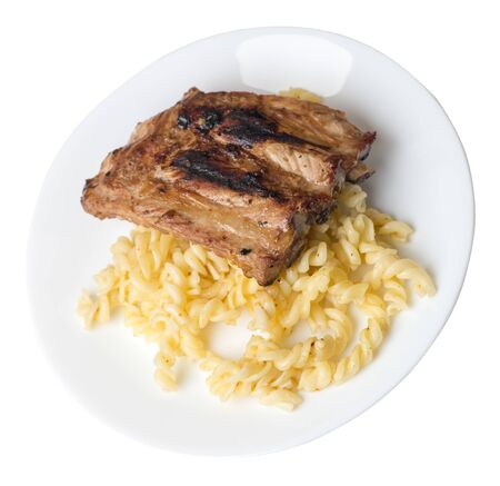 grilled pork ribs with pasta. grilled pork ribs on a white  plate isolated on white background. grilled pork ribs top view Foto de archivo - 129862580