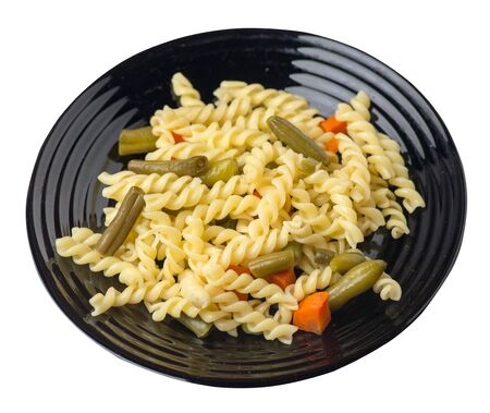 pasta with green beans with garlicand carrots on a black  plate isolated on a white background. Mediterranean Kitchen . pasta with vegetables top side view. Foto de archivo - 129862585