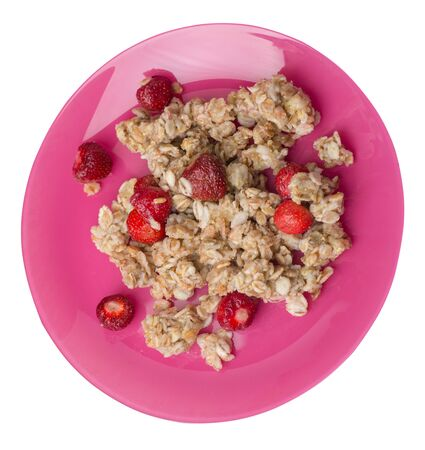 muesli with strawberries on a pink plate isolated on white background.healthy breakfast top side view.diet food on a plate.