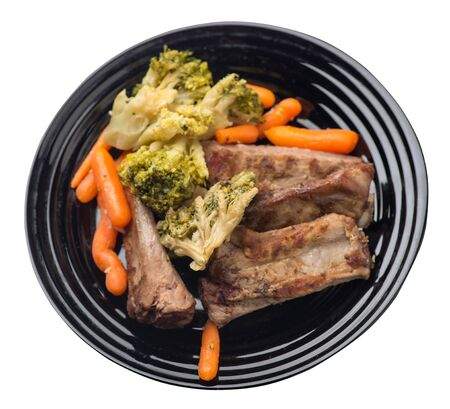 grilled pork ribs with broccoli cabbage, carrots and garlic on a black plate. fried pork ribs with vegetables on a white background. hearty rustic food top side view