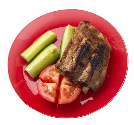 grilled pork ribs with sliced cucumbers and tomatoes on a red  plate. pork ribs isolated on white background. ribs grill top  side view Foto de archivo - 129862596