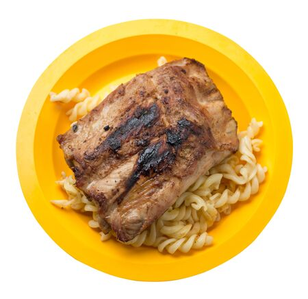 grilled pork ribs with pasta. grilled pork ribs on a yellow plate isolated on white background. grilled pork ribs top side view