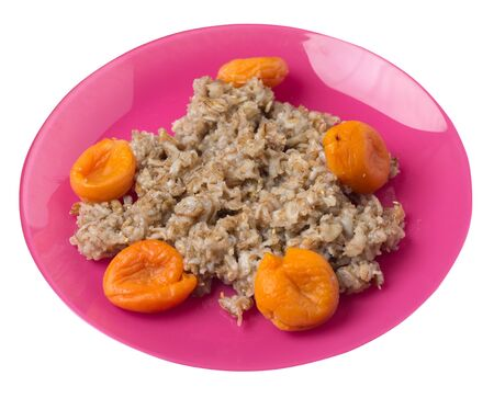 Healthy food .rzhanye flakes with dried apricots on a pink plate. rainy flakes isolated on white background. top side view diet breakfast