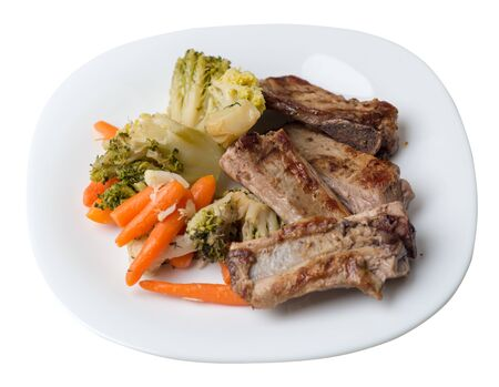 grilled pork ribs with broccoli cabbage, carrots and garlic on a white plate. fried pork ribs with vegetables on a white background. hearty rustic food top side view Stock Photo