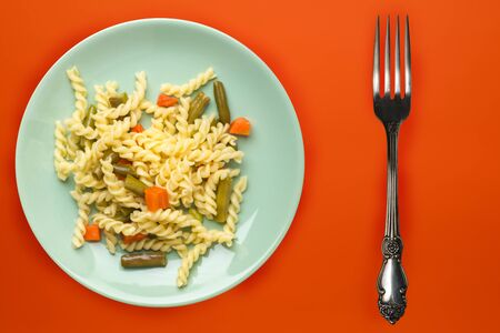 pasta on a light green plate with vegetables on a background of titanium color. Mediterranean food on an orange background. healthy food