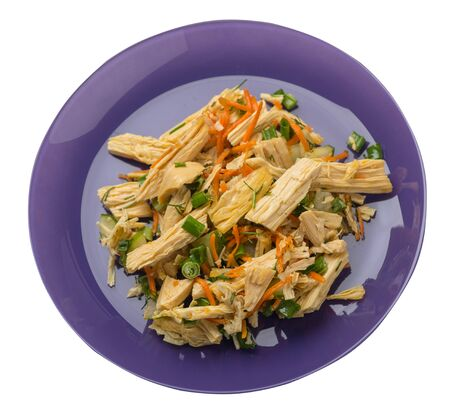 salad with soy asparagus and carrots, cucumbers and dumplings on a purple plate. vegetarian soy salad on a plate isolated on white background. healthy eating top side view.