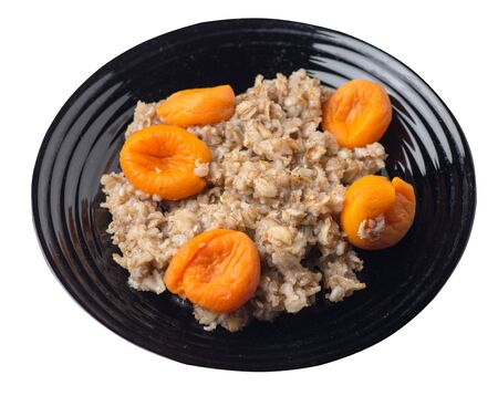 Healthy food .rzhanye flakes with dried apricots on a black plate. rainy flakes isolated on white background. top side view diet breakfast