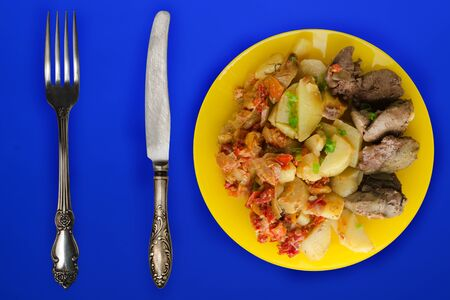 fried liver with potatoes and stewed tomatoes top view. fried liver on a yellow plate on a blue background. rustic food