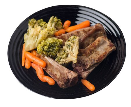 grilled pork ribs with broccoli cabbage, carrots and garlic on a black plate. fried pork ribs with vegetables isolated on a white background. hearty rustic food top side view Stock Photo