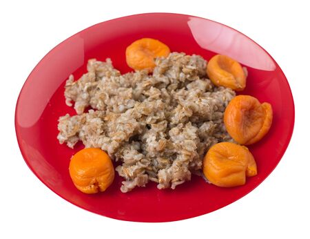 Healthy food .rzhanye flakes with dried apricots on a red plate. rainy flakes isolated on white background. top side view diet breakfast