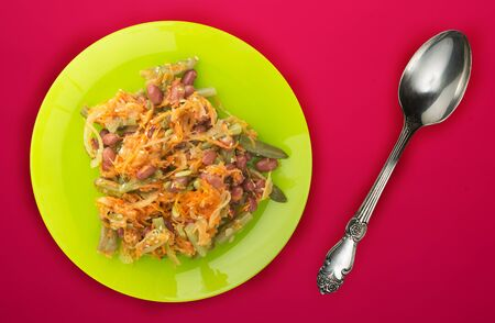 Berlin salad on a green plate on a red background. Sausage salad, cucumber, pepper top view. Stock Photo