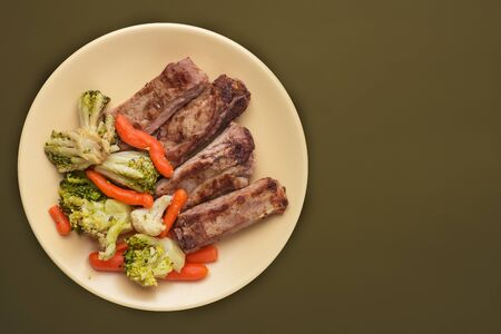 fried pork ribs with broccoli, carrots and garlic on a beige plate. fried pork ribs with vegetables against a brown green background. hearty rustic food top view
