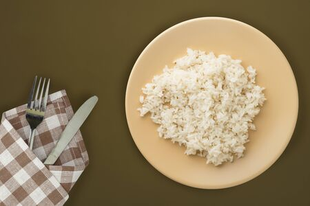 white rice on a beige plate. rice on a brown background top view .asian food