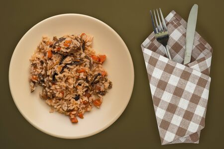 rice on a beige plate on a brown green background. white rice top view. Asian cuisine .vegetarian food