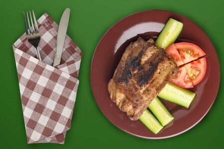 fried pork ribs with chopped cucumbers and tomatoes on a brown plate. pork ribs on an dark green background. grilled ribs top view