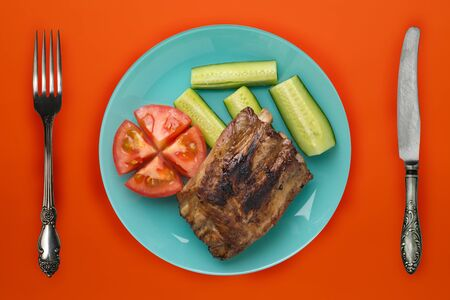 fried pork ribs with chopped cucumbers and tomatoes on a blue plate. pork ribs on an orange background. grilled ribs top view
