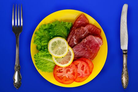 ham with lettuce, tomatoes and lemon on a yellow plate. ham on a blue background. smoked food top view