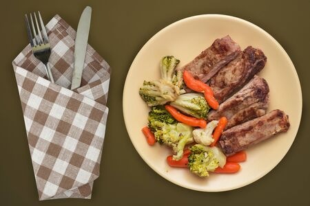 fried pork ribs with broccoli, carrots and garlic on a beige  plate. fried pork ribs with vegetables against a brown green background. hearty rustic food top view Stock Photo