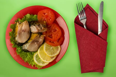 sliced mackerel with lettuce, tomato and lemon on a red plate on green background.sliced mackerel with vegetables on a plate top view.seafood