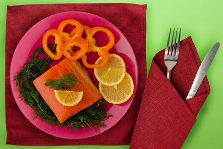 red fish with dill, pepper, lemon on a pink  plate on the green background. sea food Stock fotó