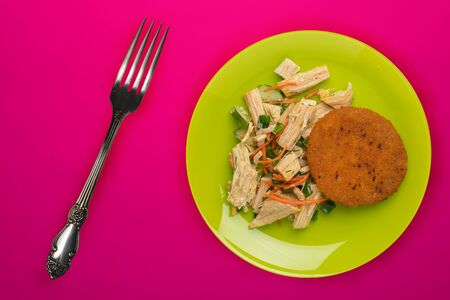 fish pie with soy asparagus and carrots, cucumbers and dill top view. fish cakes on a green plate on a red background
