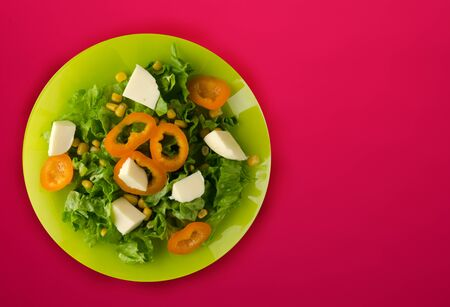 salad of cheese, lettuce, corn, pepper on a red background. Vegetarian salad on a green plate. top view vegetarian salad Imagens