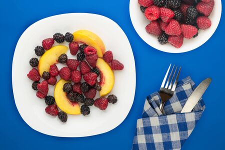 dietary, healthy food. blackberry, raspberry, nectarine on a white  plate on a plate. Vegetarian food on a blue background top view. Foto de archivo