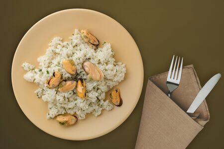 White rice with mussels on a beige plate. Rice with mussels on a brown green background. rice top view.asian food Stock fotó