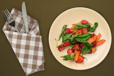 Vegetarian food . healthy food. spinach salad, apricot, strawberries on a beige plate on a brown-green background top view.