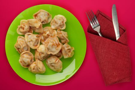 dumplings on a green plate against a red background. Dumplings meat in tomato sauce top view. Asian cuisine